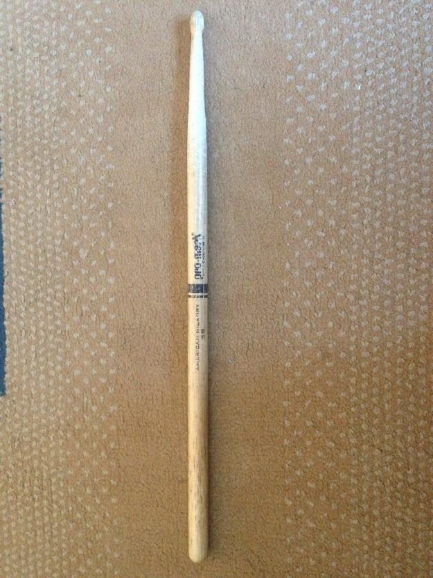 Baqueta de bateria em madeira castanha-clara oferecida pelo baterista Zé Carlos