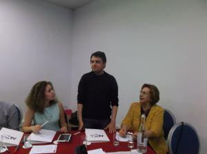 Eu, de pé, a falar atrás de uma mesa, entre a jornalista que moderou as apresentações e a presidente da CEDEMA, Maria Antónia.