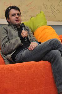 Eu, sentado num sofá cor-de-laranja, ao lado de uma grande cenoura em peluche, a falar ao microfone.