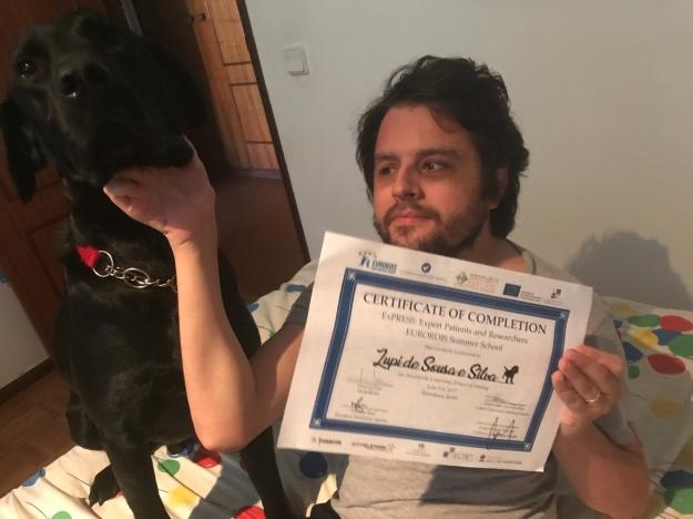 Eu a segurar um certificado de presença na escola de verão da EURORDIS, onde no nome se lê Lupi de Sousa e Silva, com um boneco de um cão impresso a seguir ao nome, e o Lupi sentado ao meu lado direito.