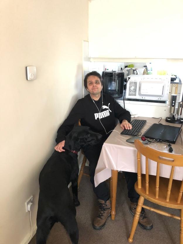 O Lupi, e eu sentado à mesa da sala/cozinha, à frente do computador portátil, com um teclado e uma  trackball ligados ao portátil, a utilizar roupa de andar por casa e ainda com as minhas botas calçadas.