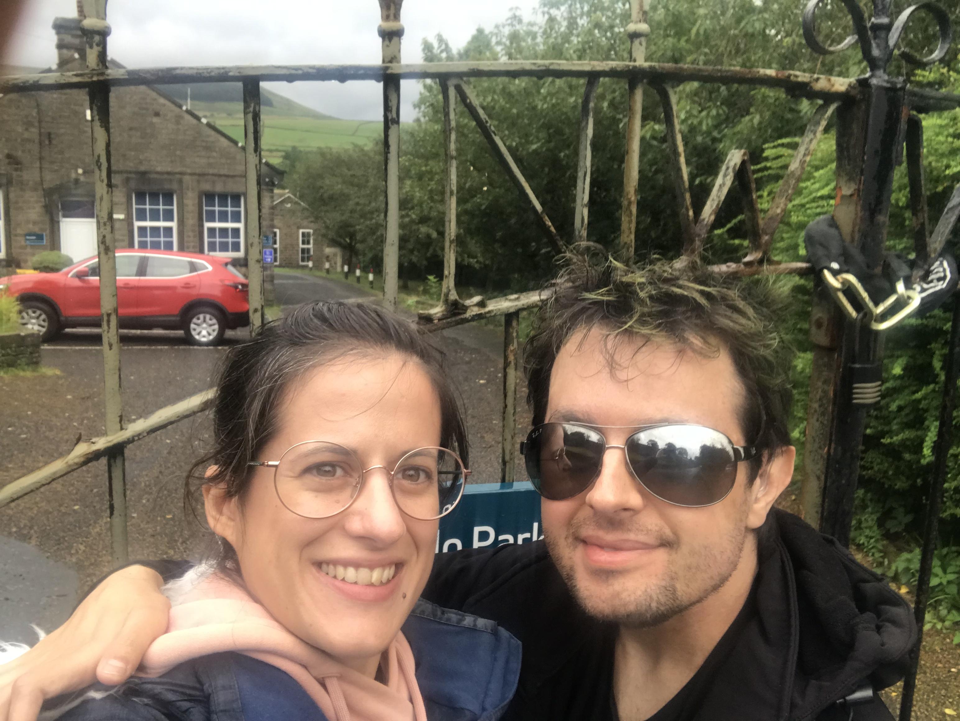 Eu e a Sofia à frente do portão trancado com o cadeado e a corrente e o carro ao fundo dentro to parque.