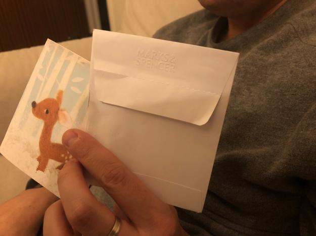 Foto de pormenor onde se vê a minha mão a segurar o cartão e o envelope.